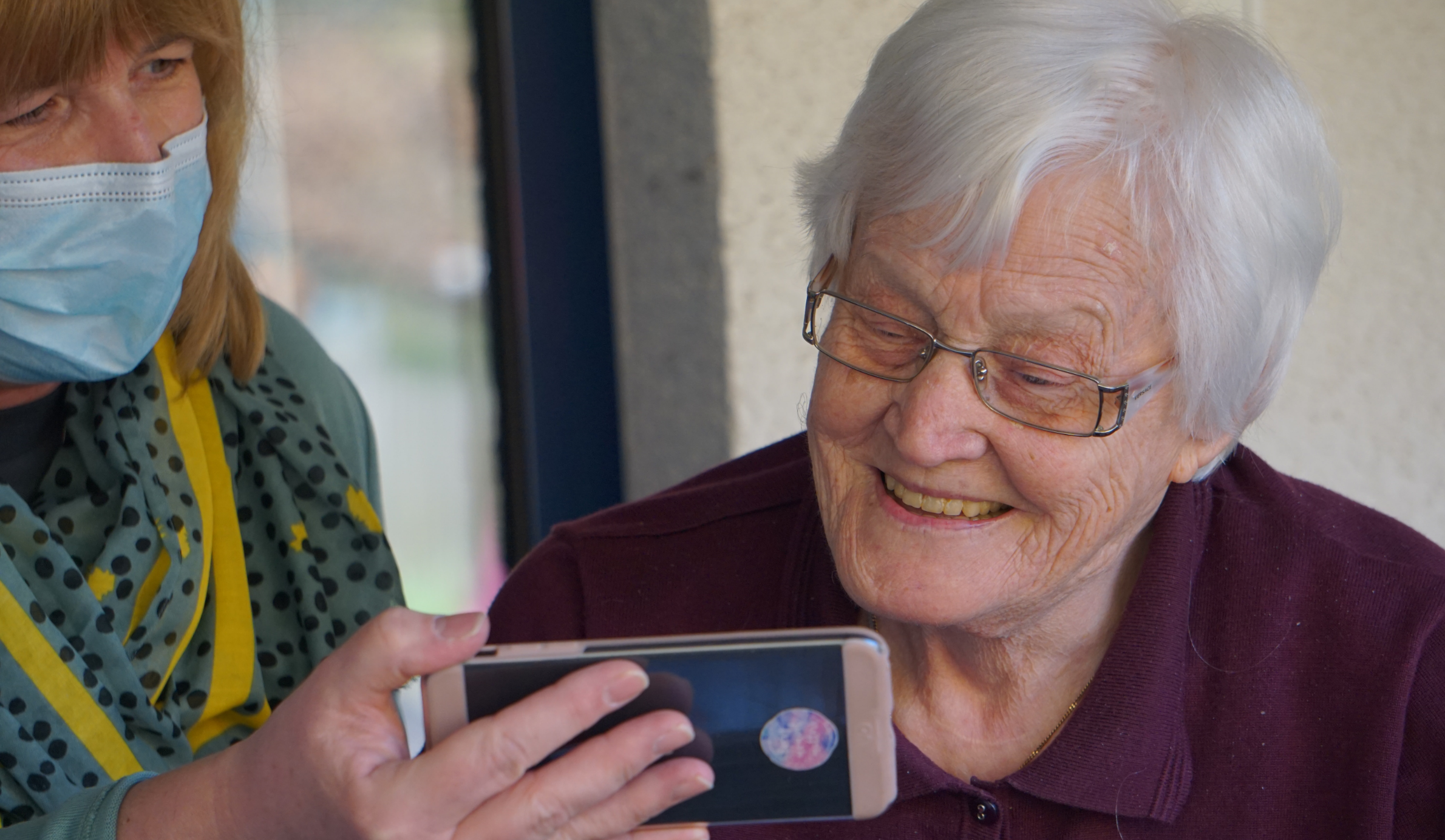 A 90 year old woman views pictures of her grandchildren on a phone. Georg Arthur Pflueger via Unsplash