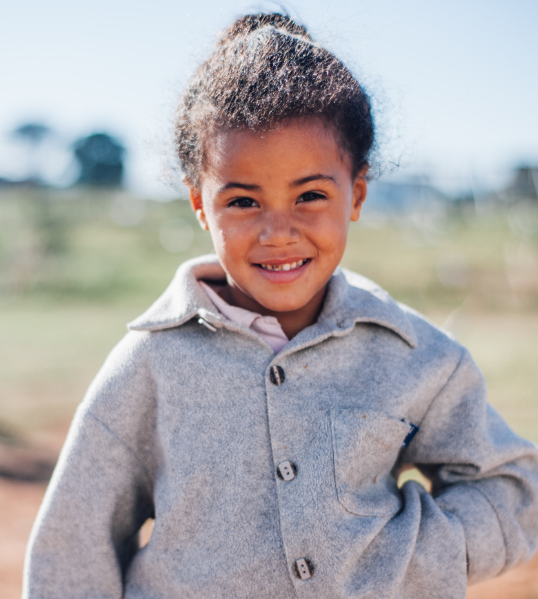 A shy little girl in South Africa – she and her family had stood in line for hours for some food that a local church was providing.
