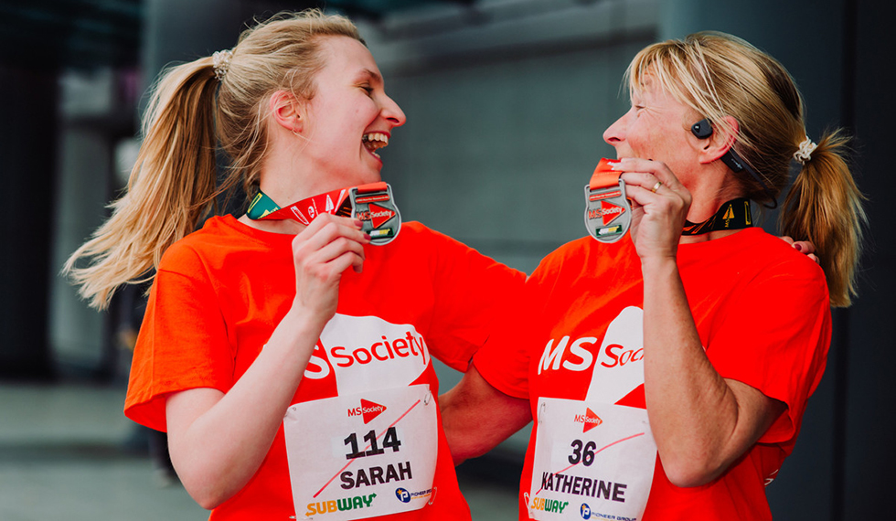 Two celebrating women wearing MS Society branded running gear